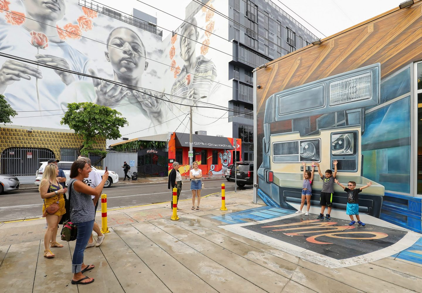 Miami, Florida, USA - December 28, 2019: Mom takes photos of her kids in front of a building ay Wyndwood.